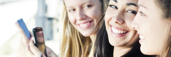 Bild: Drei fröhliche junge Frauen mit Smartphones
