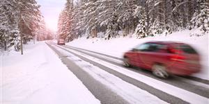 Bild: Fahrendes Auto auf schneebedeckter Fahrbahn