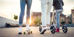 Bild: Familie auf E-Scootern fährt in Sonnenuntergang