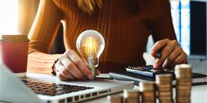 Bild: Frau am Laptop hält Glühbirne in der Hand