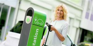 Bild: Frau an Ladestation für Elektroauto