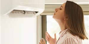 Bild: Frau bei Hitze vor Klimaanlage