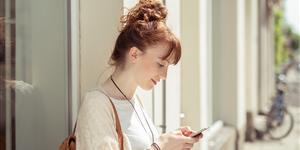Bild: Frau draußen mit Handy