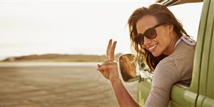 Bild: Frau in Hippiebus zeigt Peacezeichen