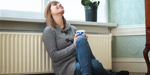 Bild: Frau lehnt an Heizung