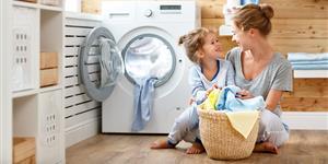 Bild: Frau mit Kind vor Waschmaschine