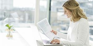 Bild: Frau mit Laptop prüft Steuerbescheid