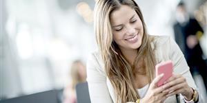 Bild: Frau mit Smartphone in Wartehalle