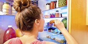Bild: Frau nascht aus dem Kühlschrank