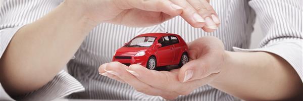 Bild: Frauenhände schützend um rotes Spielzeugauto