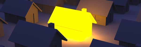 Bild: Gelb leuchtendes Hausmodell unter anderen unbeleuchteten