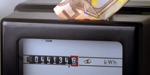 Bild: Hand steckt 50 Euroschein in Stromzähler