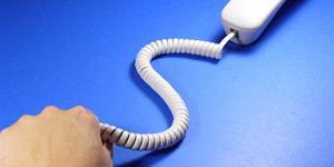 Bild: Hand zieht Hörer an Telefonschnur