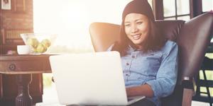 Bild: Hipster-Frau im Sessel mit Laptop und Kaffee