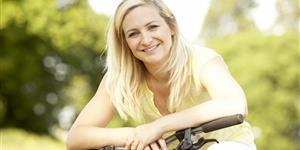 Bild: Junge Frau auf Fahrrad gelehnt