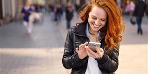 Bild: Junge Frau lachen rote Haare Smartphone Stadt