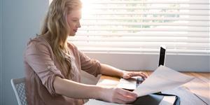 Bild: Junge Frau mit Rechnung am Laptop