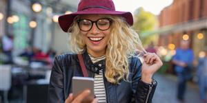 Bild: Junge Frau schaut auf ihr Smartphone