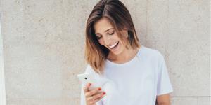 Bild: Junge Frau schaut auf Smartphone