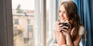 Bild: Junge Frau sitzt mit Tasse am Fenster