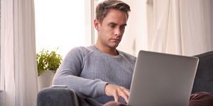Bild: Junger Mann am Laptop auf Sofa