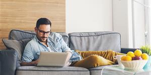 Bild: Junger Mann mit Laptop auf Couch