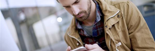 Bild: Junger Mann mit Smartphone - schräg