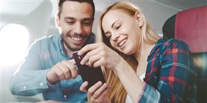 Bild: Junges Paar mit Smartphone im Fluzgzeug