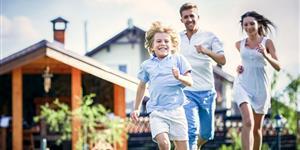 Bild: Junge Familie läuft über den Rasen ihres Gartens