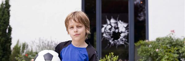 Bild: Kind mit Fußball vor kaputtem Fenster