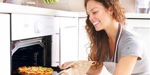 Bild: Lachende Frau holt Pizza aus dem Backofen