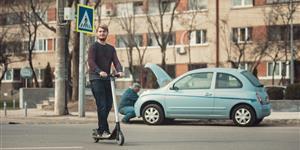Bild: Mann auf E-Scooter vor liegengebliebenem Auto