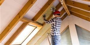 Bild: Mann bringt Dachdämmung an Gebäude an