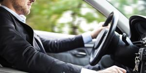 Bild: Mann im Anzug beim Autofahren