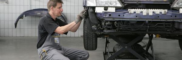 Bild: Mann repariert Fahrzeug