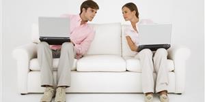 Bild: Paar auf weißer Couch mit Notebooks