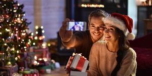 Bild: Paar mit Smartphone unterm Weihnachtsbaum