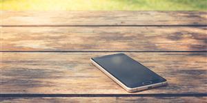 Bild: Smartphone auf Holzbank im Park