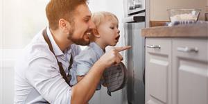Bild: Vater mit Sohn in der Küche am Backofen