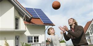 Bild: Vater und Sohn beim Ballspielen vor Haus mit Solar-Dach