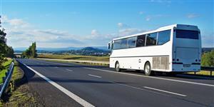 Bild: Weißer Reisebus auf einer Landstraße