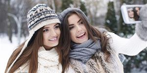 Bild: Zwei Frauen machen Selfie mit Smartphone in Winterlandschaft
