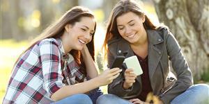 Bild: Zwei junge Mädchen mit Smartphones im Freien